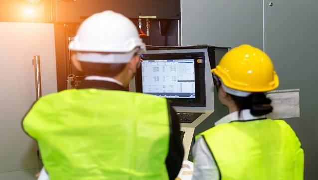 Female and male engineers are inspecting machine operations and controlling product quality.